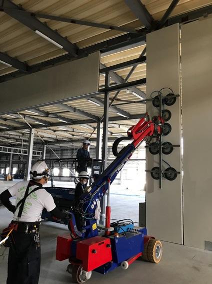 ジラフという機械でパネルをつかみ壁面に設置していきます